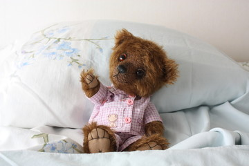 Teddy bear resting on the bed in pajama