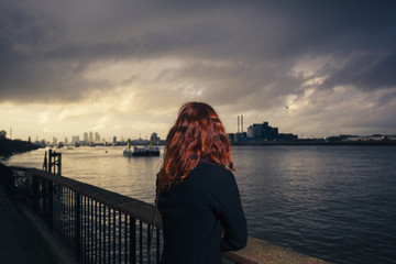 Woman admiring sunet over river in city