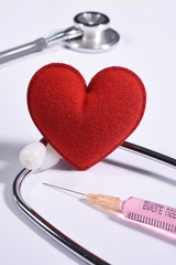 Red heart on stethoscope and a syringe on  white background.