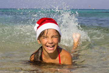 Little girl in the hat of Santa Claus swims in the sea