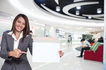 Young brunette businesswoman showing blank signboard