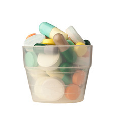 Small cup filled with pills and capsules isolated