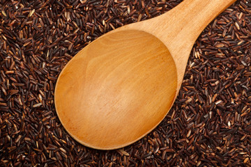Wooden spoon on Thai Red Cargo rice