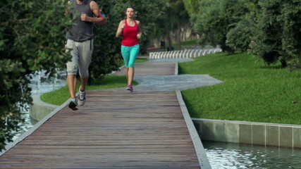 Young couple jogging in city park slow motion, shot at 120fps