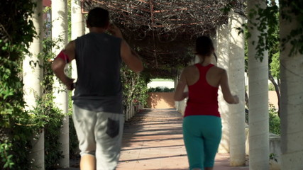 Young couple jogging in park tunnel