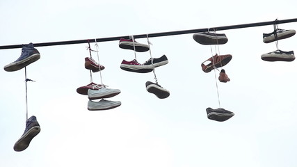 Pairs of shoes hang tossed telephone wire, sneakers power lines