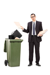 Angry businessman throwing his stuff in the trash