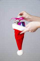 Woman putting money in a Santa hat on gray background