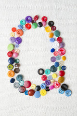 Letter Q of the alphabet of buttons of various shapes and colors