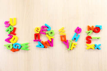 Love word formed with colorful letters on wooden table