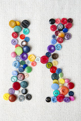 Letter K of the alphabet of buttons of various shapes and colors
