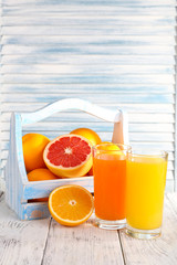 Orange and carrot juice in glasses and fresh fruits in wooden