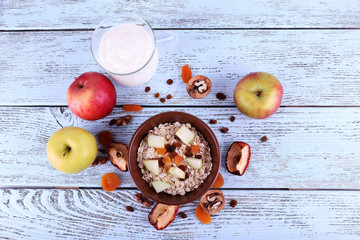 Bowl of oatmeal, walnuts, dried apricots, apples and yogurt