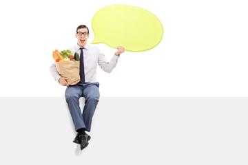 Man with groceries holding a speech bubble