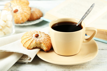 Cup of coffee with tasty cookie on color wooden background