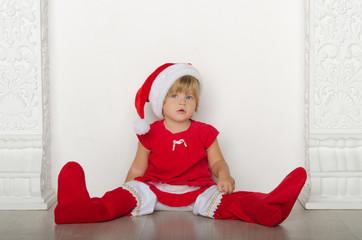 girl in costume of Santa Claus sitting on floor