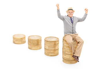 Joyful senior seated on a pile of coins