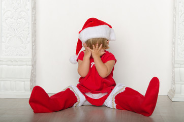 girl in costume of Santa hides his face