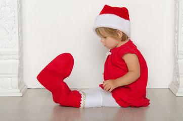 girl in costume of Santa looks at his feet