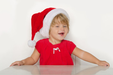 girl in costume of Santa Claus at table and smiling