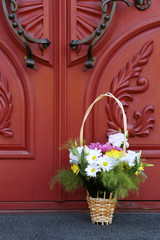 Flowers in basket on wooden door background