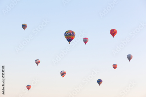 Multicolored balloons in flying in sky, sunrise time - 73292312