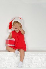 girl in costume of Santa sitting on fireplace