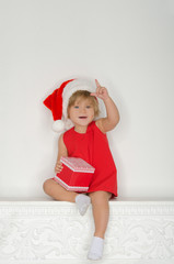 girl in costume of Santa Claus sitting on fireplace