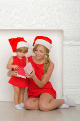 woman with a child in Santa costumes look gift