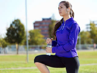 Pretty young woman drinking water after running.