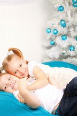 Happy kids hugging near the Christmas tree.