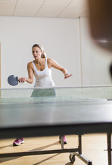 Attractive young woman returning the ball in table tennis