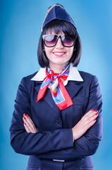 Charming stewardess dressed in bkue uniform. Sunglasses.