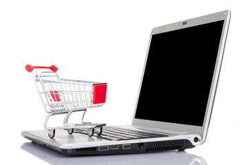 Shopping cart over a laptop computer, isolated on white backgrou