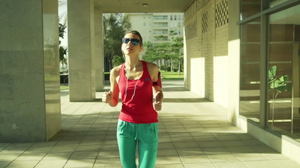 Sportive woman jogging in the city on a sunny day, slow motion