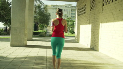 Attractive woman jogging in the city on a sunny day, slow motion