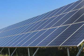 Row of solar panels on blue sky
