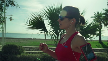 young sportive woman running close to the city beach