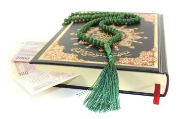 zugeschlagener Koran mit iranischer Währung