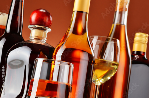 Bottles and glasses of assorted alcoholic beverages - 73298954