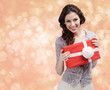 Pretty woman hands a present wrapped in red paper