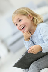 Little blond girl using tablet with thoughtful expresssion