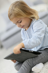 Cute blond little girl watching movie on tablet