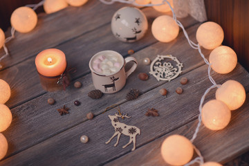 on wooden table lit garland and candle in a cup of coffee and nu