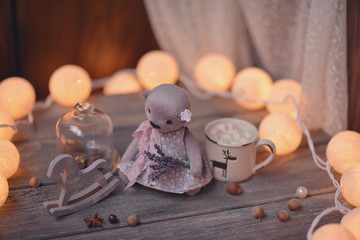 on wooden table lit candle and garland and a wooden horse and be