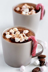Mug of hot chocolate with marshmallows and candy cane