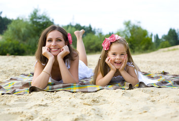 Mother and daughter having a rest on a beach