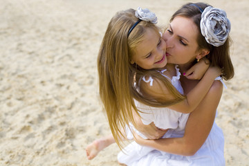 Mother and daughter in white sundresses on beach