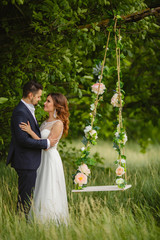 Beautiful bride with fiance is swinging on a swing