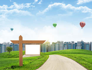 Tall buildings, green hills and road with wooden signboard